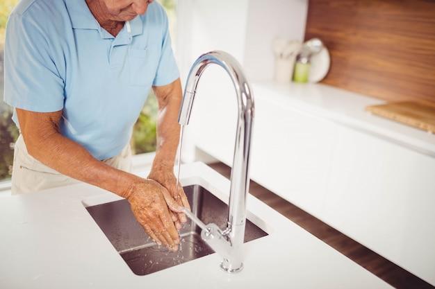 Seção intermediária do homem sênior, lavar as mãos na cozinha