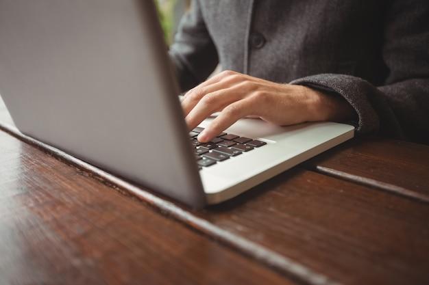 Seção intermediária do homem usando laptop