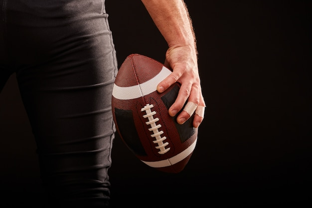 Seção intermediária do jogador de futebol americano com bola contra preto, copie o espaço, vista traseira