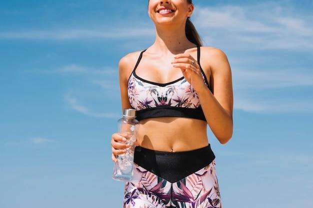 Seção intermediária do jovem atleta feminina fitness correndo contra o céu azul