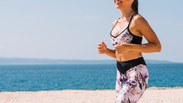 Seção intermediária do jovem fitness feminino corredor correndo perto da praia