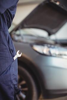 Seção intermediária do mecânico com uma chave inglesa no bolso