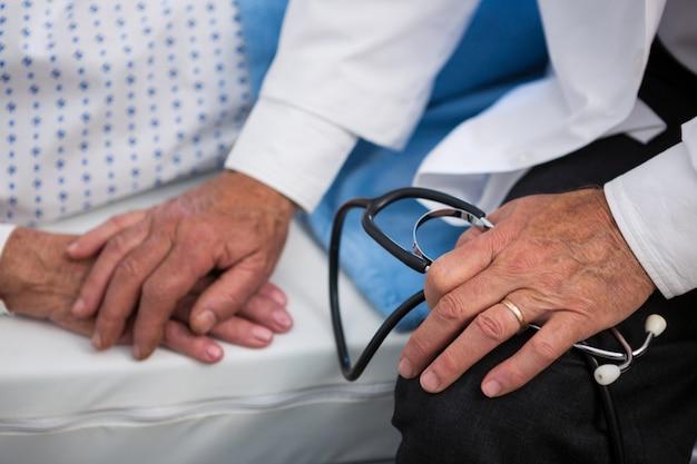 Seção intermediária do médico consolando paciente sênior