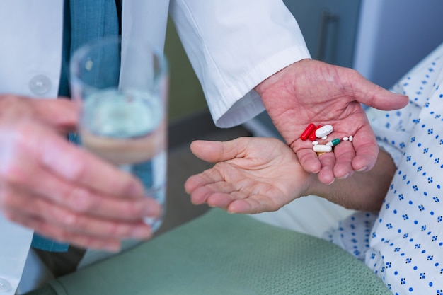 Seção intermediária do médico dando pílula ao paciente