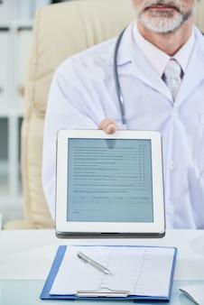 Seção intermediária do médico sentado à mesa, estendendo o questionário digital na tela do tablet para a câmera