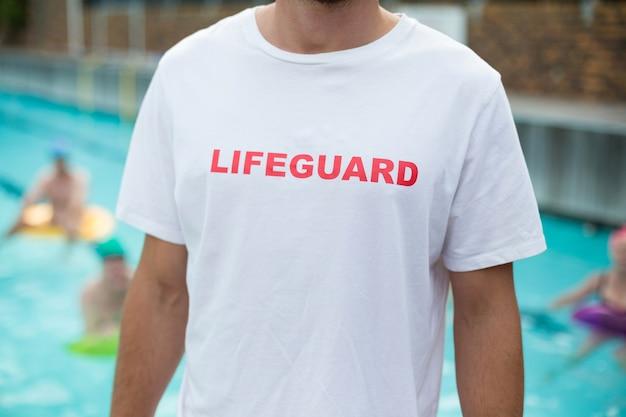 Seção intermediária do salva-vidas masculino em pé à beira da piscina