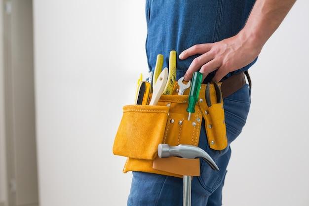 Seção intermediária do trabalhador manual com cinto de ferramentas em volta da cintura