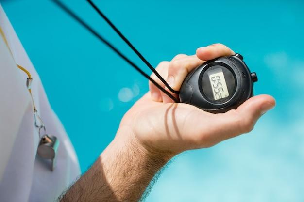 Seção intermediária do treinador de natação segurando um cronômetro perto da piscina
