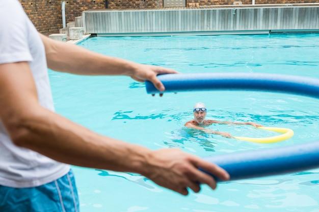 Seção intermediária do treinador demonstrando o uso de macarrão de piscina