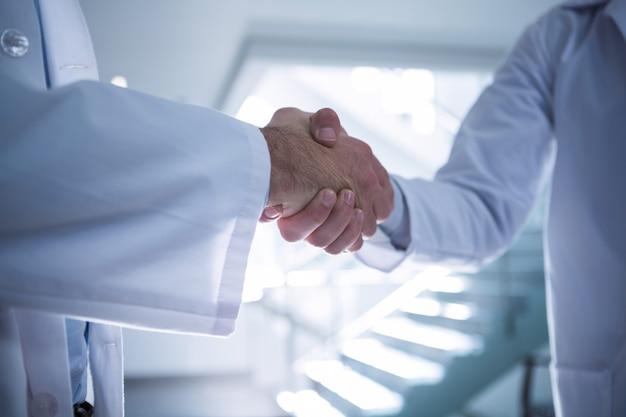 Seção intermediária dos médicos, apertando as mãos no corredor