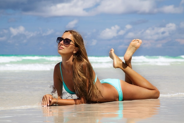 Seção meados de da jovem mulher no biquini azul que sunbathing na areia branca. menina da moda de bronzeamento na praia tropical