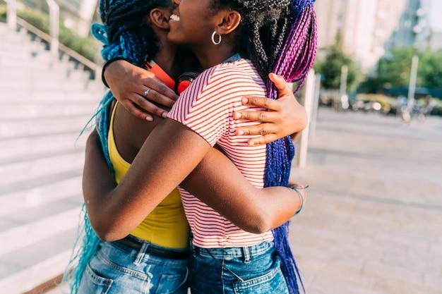 Seção média, duas irmãs, ao ar livre, abraçando, sorrindo