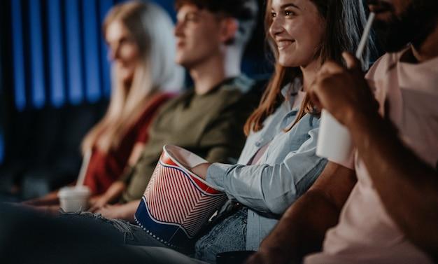 Seção mediana de jovens alegres irreconhecíveis sentados no cinema, assistindo a um filme.
