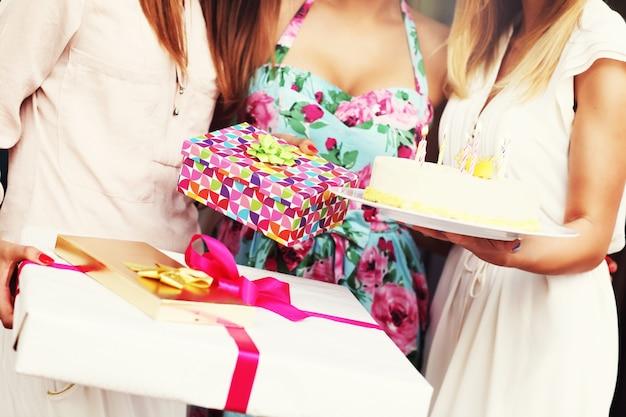 Seção mediana de mulheres segurando um bolo de aniversário e presentes