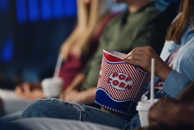Seção mediana de uma jovem irreconhecível com pipoca no cinema, assistindo o filme.