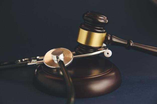 Seção mediana do juiz golpeando o martelo com estetoscópio na mesa do tribunal