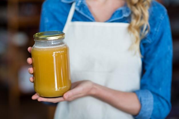 Seção mestra da equipe feminina segurando o pote de mel