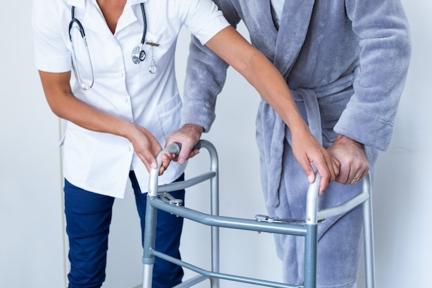 Seção mestra da médica, ajudando o homem sênior a andar com walker