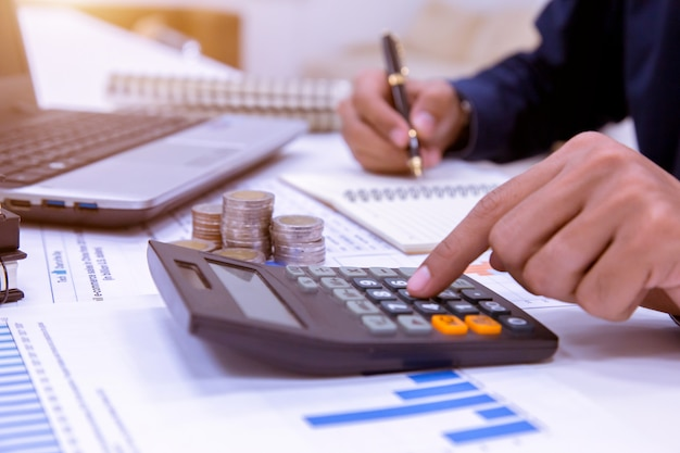 Seção mestra de calculadora tax using tax do homem de negócios no escritório.