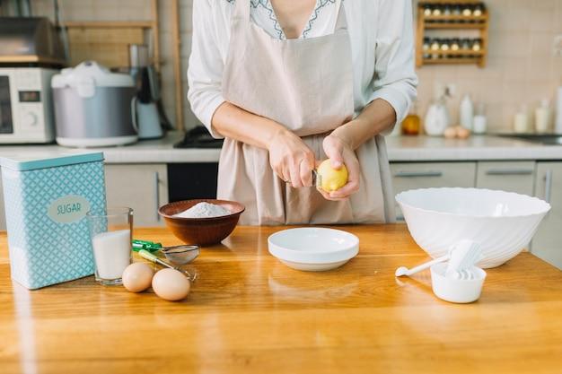 Seção mestra de uma mulher que rala o limão ao preparar o bolo