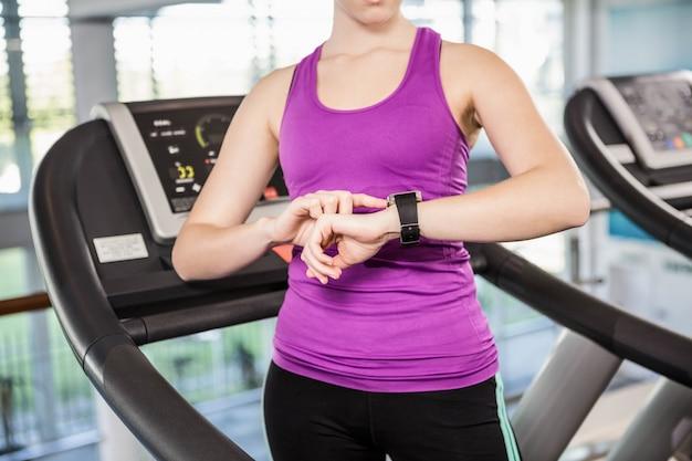 Seção mid, de, ajustar, mulher, usando, smartwatch, ligado, treadmill, em, a, ginásio