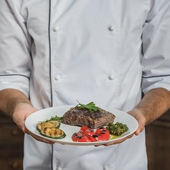 Seção mid, de, macho, cozinheiro, segurando, preparado, bife carne, com, legumes