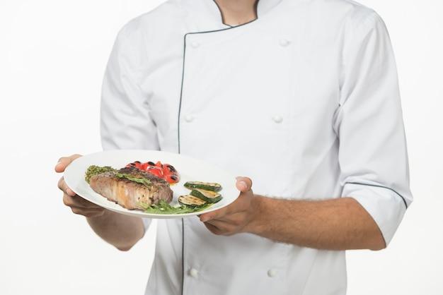 Seção mid, de, macho, cozinheiro, segurando, preparado, prato, com, bife assado, e, legumes