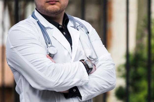 Seção mid, de, um, doutor masculino, com, estetoscópio, ao redor, seu, pescoço, ficar, com, braço cruzou