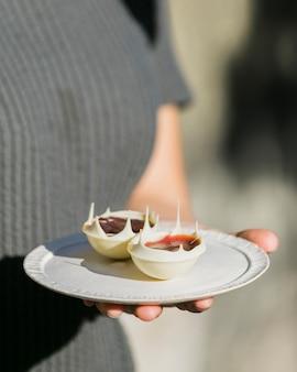Seção mid, de, um, mulher segura prato, com, branca, sobremesa chocolate