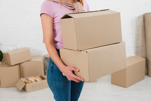 Seção mid, ligado, um, mulher jovem, segurando, pilha, de, caixas cartão