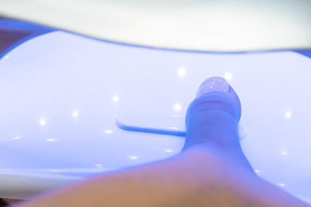 Secar as unhas após a aplicação de verniz em um secador ultravioleta especial
