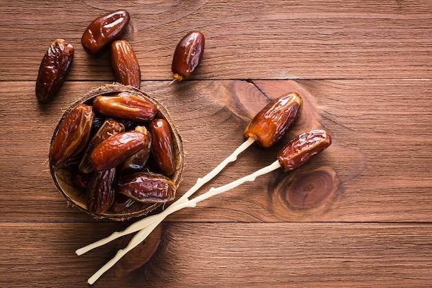 Secas doces datas frutas na tigela, pauzinhos para comer na madeira. vista do topo