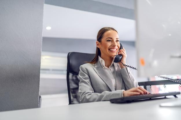 Secretária amigável linda jovem sentado em seu escritório