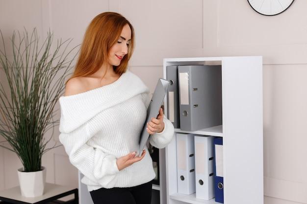 Secretária com uma pasta perto das prateleiras do escritório