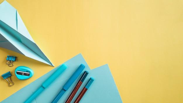 Secretária criativa com artigos de papelaria na parede amarela