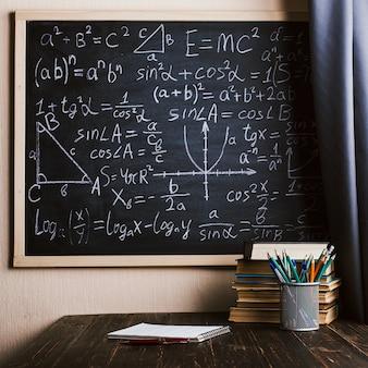 Secretária de escola em sala de aula, com livros sobre fundo de quadro de giz com fórmulas escritas