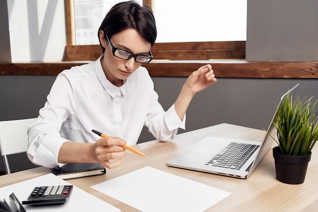 Secretária de mulher de negócios de camisa branca sentada a uma mesa em frente a um laptop