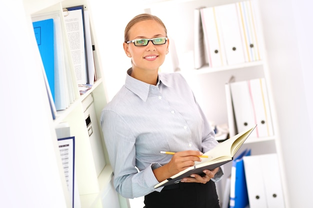 Secretária de sorriso com o caderno aberto