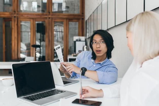 Secretária loira sentada com o telefone ao lado do laptop com tela preta e ouvindo jovem asiático de óculos. trabalhador de escritório chinês morena falando com a gerente feminina de blusa branca.