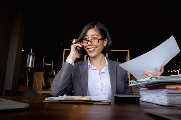 Secretária ocupada que fala com o cliente pelo telefone de pilha.