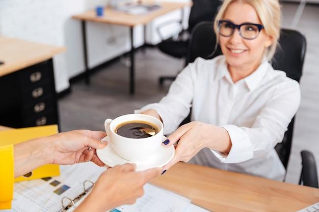 Secretária trazendo uma xícara de café para o chefe sorridente no escritório