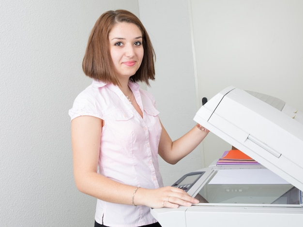 Secretária usando uma copiadora no escritório