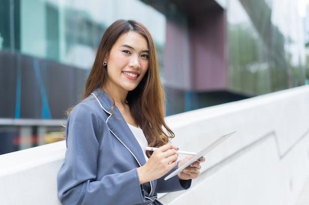 Secretário de jovem empresária segurando o tablet com caneta no escritório exterior
