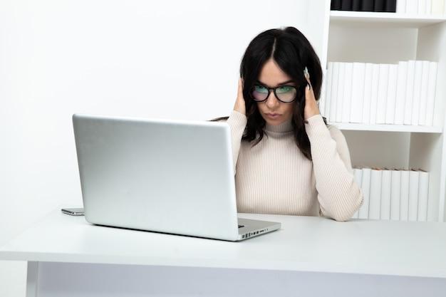 Secretário de mulher cansada, sentindo-se mal sentado no armário do escritório branco.