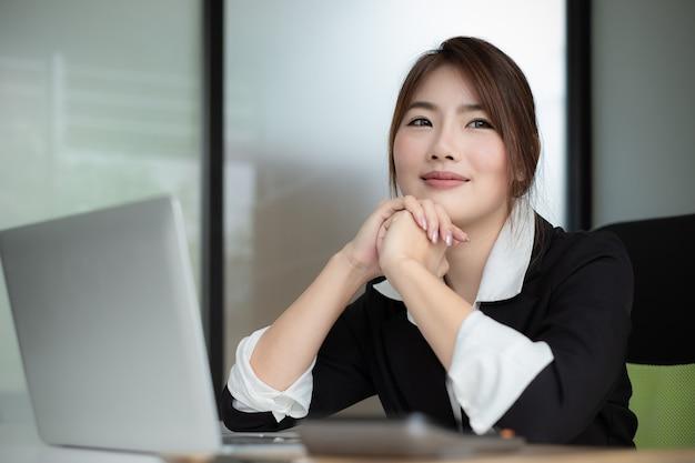 Secretário fêmea novo que sorri, pensando, apreciando no trabalho