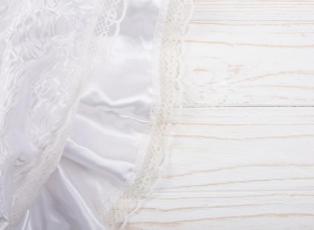 Seda branca e renda contra um fundo branco de madeira