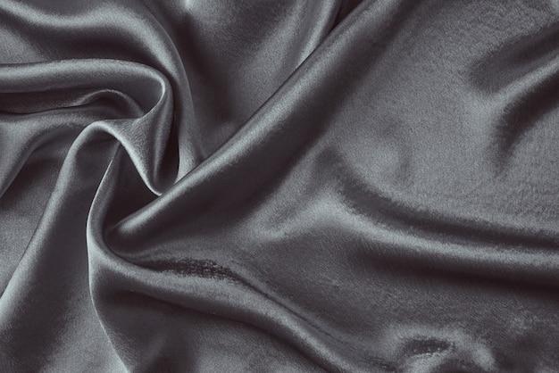 Seda escura com pregas. textura abstrata da superfície de cetim ondulada