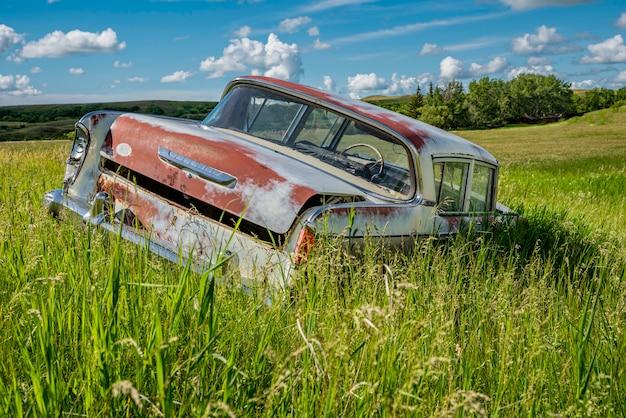 Sedan azul antigo abandonado na grama alta na encosta de uma colina