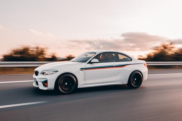 Sedan branco do esporte com ajuste colorido na estrada.