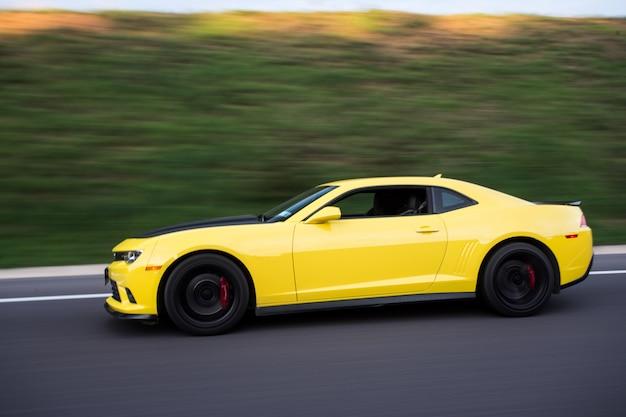 Sedan de esporte amarelo na estrada, vista lateral.